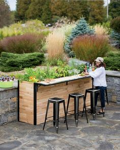 """Gardener's Supply Company is now offering a wooden outdoor cocktail bar that doubles as a planter. Made with solid and reclaimed cedar planks, the """"Plant-A-Bar's"""" bar easily unfolds when desired."""