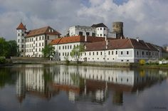 Jindřichův Hradec is situated in southeastern Bohemia between a lake and a river as a means of defense on the flat plain on which the castle is situated. Jindřichův Hradec has a history that dates back to the 13th century, and older parts of the castle have been incorporated into newer additions. A chateau, which was added later, is also a part of the grounds. Chapels with frescoes from the 14th century make up the oldest part of the complex.