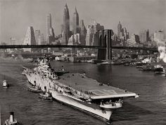 The USS Tarawa passes under the Brooklyn bridge