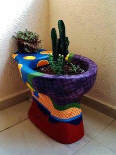 bunter blumentopf mit pflanzen aus altem toilettenbecken