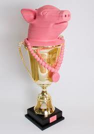 Ted Noten, 2010, onderscheiding voor eind examenkandidaten van de Design Academy te Eindhoven. Roze varkenskop met parelketting. Op de beker is het logo van de Designacademy aangebracht en de parelketting en de varkenskop zijn op de beker aangebrachte symbolen. het varken staat voor vernieuwing in kunst en design.