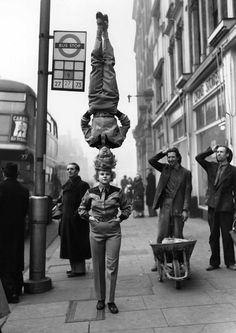 Two members of the Bertram Mills Circus walk head-to-head at Hammersmith Broadway in London, 1953.