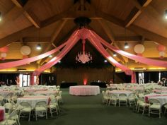 """Keeneland Entertainment center ceiling drape. We used pink drape with twinkle lights. Paper lanterns and the center is a foam board """"chandelier"""" provided by the client."""