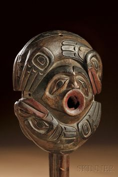Rare Northwest Coast Shaman's Rattle, c. 1840-60, probably Tlingit, carved in two pieces with central mask-like face on each side, with pierced circular mouth, framed by two relief carved seals in profile, red and black pigment, ht. 9 1/4, wd. 3 7/8 in.