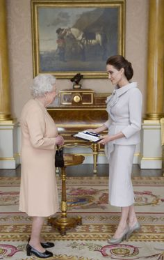 The Queen presents the insignia of an Honorary Dame Grand Cross of the Most Distinguished Order to Angelina Jolie.