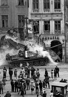 A Soviet T-62 medium tank smashing into a house in Prague (1968):