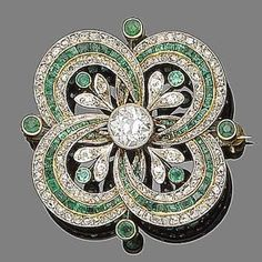 An emerald and diamond brooch/pendant, ca 1915. Centrally-set with an old brilliant-cut diamond within an openwork quatrefoil set with alternating rows of calibré-cut emeralds and rose-cut diamonds, accented with circular-cut emerald and single-cut diamond flowers, principal diamond approx. 0.85ct, #DiamondBrooches