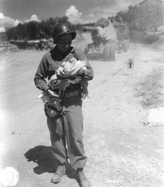 Un cameraman d'une Signal Photo Company, un bébé dans les bras. Dans sa main…