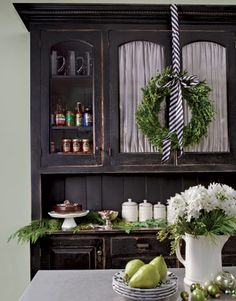 boxwood wreath with black and white striped ribbon. I adore the greenery against the dark colours
