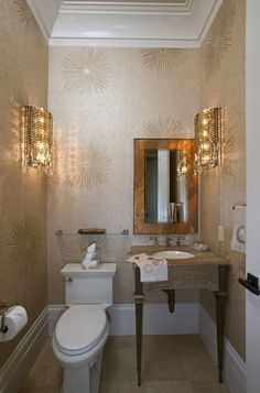 glamour sparkling in this small powder room, whether from the large-scale gold wallpaper or the sconces that resemble dangled earrings.     Tip: Don't assume you need to go small with your moldings in a small room. The wide and layered moldings at the baseboards and ceiling are well-proportioned here.  #powderroomjewelbox
