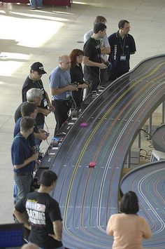2008 World Slot Car Racing Championships, held at the centre:mk (Milton Keynes Shopping Centre), England, 11-18 October 2008     Slot cars are powered small vehicles that are assisted by a slot or groove set in the tracks on which they run. At the bottom of the car is a blade or pin that keeps the car in the slot. To make the car run, the metal strips placed next to the slot d