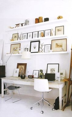Minimal workspace décor with leaning artwork on open shelves