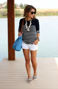 black/white striped tee white shorts neutral flats green handbag multi-strand pearls