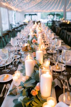 something like this for the long tables - garland of eucalyptus with flowers. ivory table linens, pillar candles in clear vases