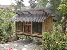 An outdoor duplex rabbit hutch in tropical country, the wall and the floor are made of bamboo.