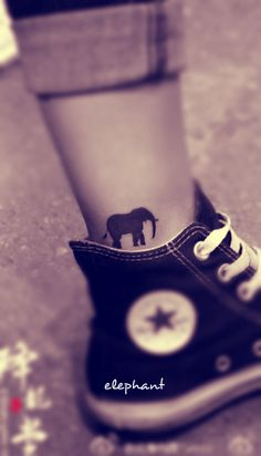 a small black elephant tattoo on the ankle