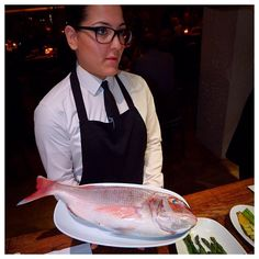 A waiter giving a fish that a guest has chosen to the chefs and explaining how it is to be prepared. Fresh!