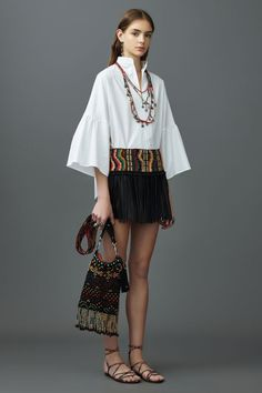 200+ best looks of Resort 2017: Valentino presents a boho look with his pairing of a geometric woven belt, fringe mini, and a wide sleeved top.