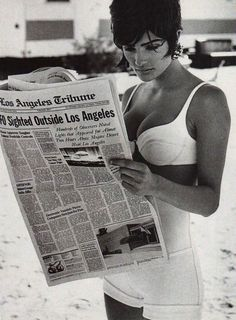 "Helena Christensen reading the Los Angeles Tribune in ""Verso Il 2000"" for Vogue Italia, March 1990. Photographer: Peter Lindbergh. Stylist: Elizabeth Dijan.""UFO Sighted Outside Los Angeles. Hundreds of Observers Noted Lights that Appeared for Almost Two Hours Above Mojave Desert Near Los Angeles."""