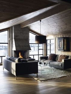 Concrete fire place with modern couches and wood walls