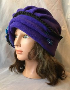 Very pretty winter warm hat ..double layer of fleece velour in purple and grey colors. decorated with hand made wet felted flower out of merino wool and bamboo silk , beaded, i love the fit of this style hat !will fit up to 23.inches heads . .Mannequin head size is 21 inches .i use two days priority shipping for USA customers . Thanks
