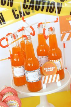 Great idea for a kids construction party, plain glass bottles filled with bright orange slush and finished off with some great construction straws.