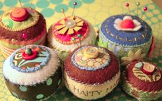 A few fabric scraps, some felt, some funky buttons. Put them all together with some blanket stitches and voila...pincushions good enough to eat (minus the pins, of course...)