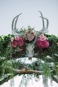 Rustic-chic wedding ceremony decor idea - arbor decorated with greenery + pink flowers with skull {BACIO Photography}