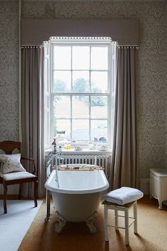 Upstairs at the Inchyra Estate, the elegant bathroom features taupe curtains, a matching claw-foot bathtub and a view to the garden.