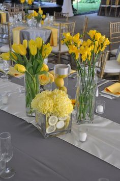 Gray table cloth, white runner, purple napkins and flowers. Like the idea of diff flowers in diff vases.