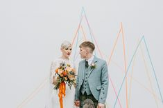 Bride in Sassi Holford Wedding Dress and Lace Cape and Groom in Tartan Kilt and Tweed Jacket Standing in Front of Bright Geometric Wall Art Geometric Wall Art, Geometric Shapes, Tartan Kilt, Geometric Wedding, Sophia Webster, White Wedding Dresses, Tweed Jacket, Bridal Boutique, Bridal Shoes