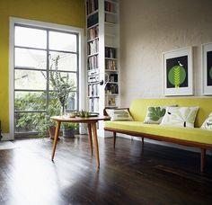 Bookshelves around corner, yellow pop of color, living room, dark wood floor