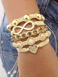 Kit de 5 pulseiras confeccionadas em macramé na cor bege, sendo:  - 1 pulseira com coração dourado e strass topaz  - 1 pulseira de corrente de strass topaz  - 1 pulseira de perolas douradas  - 1 pulseira de cristais facetados bege  - 1 pulseira com símbolo do infinito    > Pulseiras ajustáveis, nosso padrão ajusta bem em pulso de 15-18 cm. Caso você tenha um maior ou menor, informe no pedido o tamanho do seu pulso que faremos personalizada para melhor ajuste. Para medir seu punho, use uma…