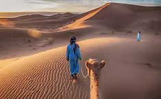two tuareg nomads leading a camel in the sahara desert morocco. Excursion Marrakech, Road Trip, The Dunes, Morocco, Camel, Sunrise, Photo Editing, Deserts, Royalty Free Stock Photos