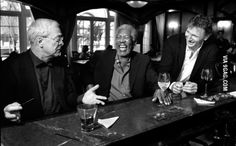 Morgan Freeman and Liam Neeson laughing at a joke Michael Caine told while all three are sitting at a bar.