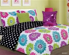 Flower Design Girl /Teen Bedding Set. Splashes of large flowers all over in pink, purple, lime and aqua on a white background. The reverse side of the comforter features black with white polka dots. This comforter bedding set comes with a purple sequined pillow and a furry lime green pillow.