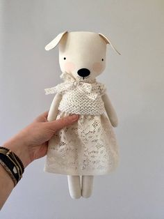 This puppy comes in a hand knit sweater, a lace skirt and a lace ribbon at her neck. Her clothing is designed to be removable, but please keep in mind that some of the fabrics may be delicate and should be taken on and off with care. Clothing should be taken on and off over the body rather