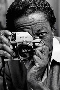 by Bruce Davidson  Photographer and director Gordon Parks looks through a Nikon camera, 1970.