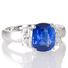 An oval blue Sri Lankan sapphire and diamond cluster engagement ring. View our collection of antique, Art Deco, and modern jewellery at www.rutherford.com.au