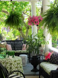 Southern porch - I love the lush, healthy ferns hanging down to add color and beauty to the space. Mixed in with vibrantly blooming plants hanging down or on the porch itself, it adds an outdoor living space that everyone will want to spend time in.