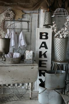 Farmhouse fresh display @ our shop featuring a neutral white palette - full of galvanized containers, metal bakery sign, wall décor, cotton, tea towels, metal baskets, wall hooks, olive buckets, vintage sprinkling cans, a vintage drop leaf table, large galvanized serving platters, metal cake stands, hanging pendant lights & more Timeworn Treasures | Danville, PA  Decorating, Zinc, Farmhouse style, Shabby Chic, Chippy, Store Displays, Shop Inspiration, Display ideas, Kitchen