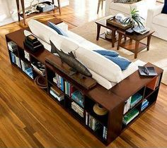 Bookshelves wrapped around couch    Forget end tables. These bookshelves fulfill your need for end tables next to the couch, while also elegantly storing books and knickknacks.