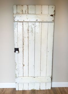 A old antique door with is original patina and door knob. It is mostly white on both sides with some chippy spots revealing some browns and green