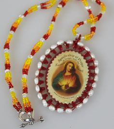 jesus sacred heart, religious pendant, double sided, wire wrapped in freshwater pearls, double strand fire color necklace with heart closure $19.00
