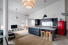 Loft-asunnon musta keittiö betonitasoilla