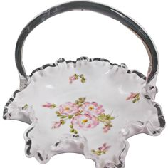 A vintage unmarked Fenton Silver Crest basket with hand painted roses.  Measures seven and three quarter inches wide and six and a quarter inches tall
