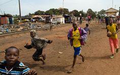 Kids playing alongside train track in Conakry, Guinea