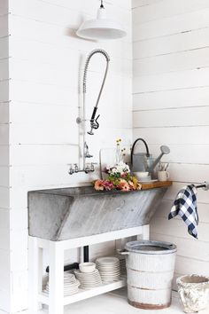 A vintage farmhouse sink at the back of the store is used for watering flowers and rinsing the occasional dish. sink laundry room Shopper's Diary: Salt House Mercantile on Bainbridge Island, Washington - Remodelista Rustic Laundry Rooms, Laundry Room Sink, Farmhouse Laundry Room, Vintage Laundry Rooms, Outdoor Laundry Rooms, Laundry Room Island, Laundry Tubs, Basement Laundry, Small Laundry