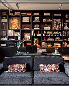 Como home office e living são totalmente integrados, a arquiteta Gabriela Marques projetou uma estante que serve aos dois ambientes. Na sofisticada cor preta, ela abriga livros, revistas, obras de arte, fotos e objetos de decoração