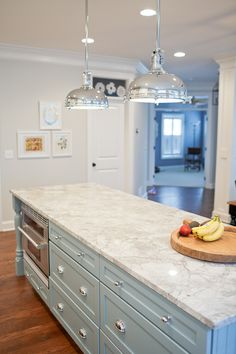 pale blue island with white countertop, nickel hardware and lighting.  Light and sparkly space.